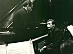 Photograph of Glenn Gould seated at the piano and talking to Walter Susskind, December 1960